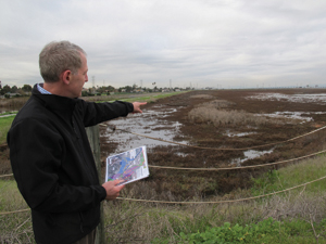 Photo: Len Materman points to the marsh that will receive flood water after the San Francisquito Creek levee is lowered, making homes near the marsh and creek safer as well as providing habitat benefits. Photo by Susan K. Moffat.