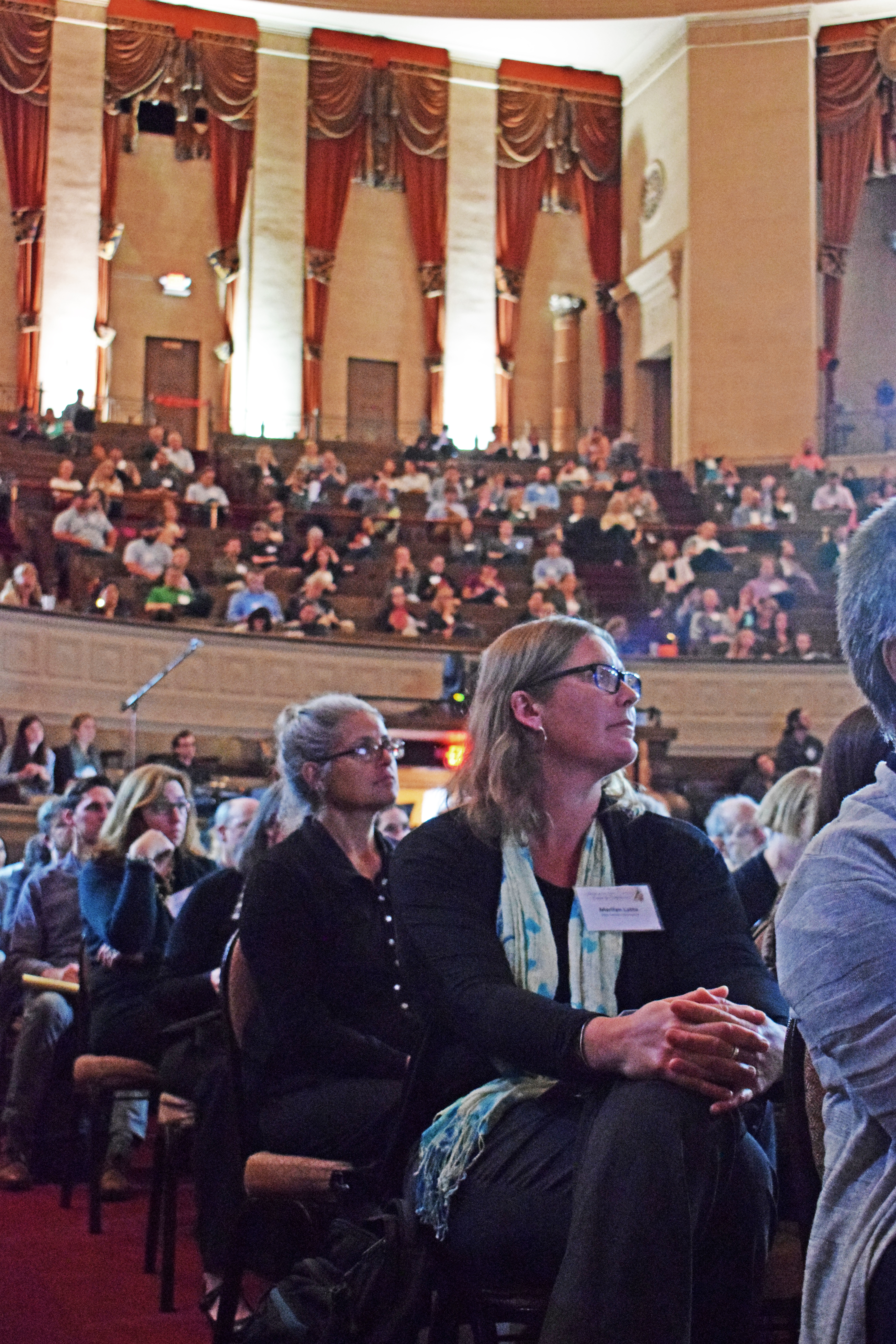 Woman sitting in large auditorium for conference plenary session