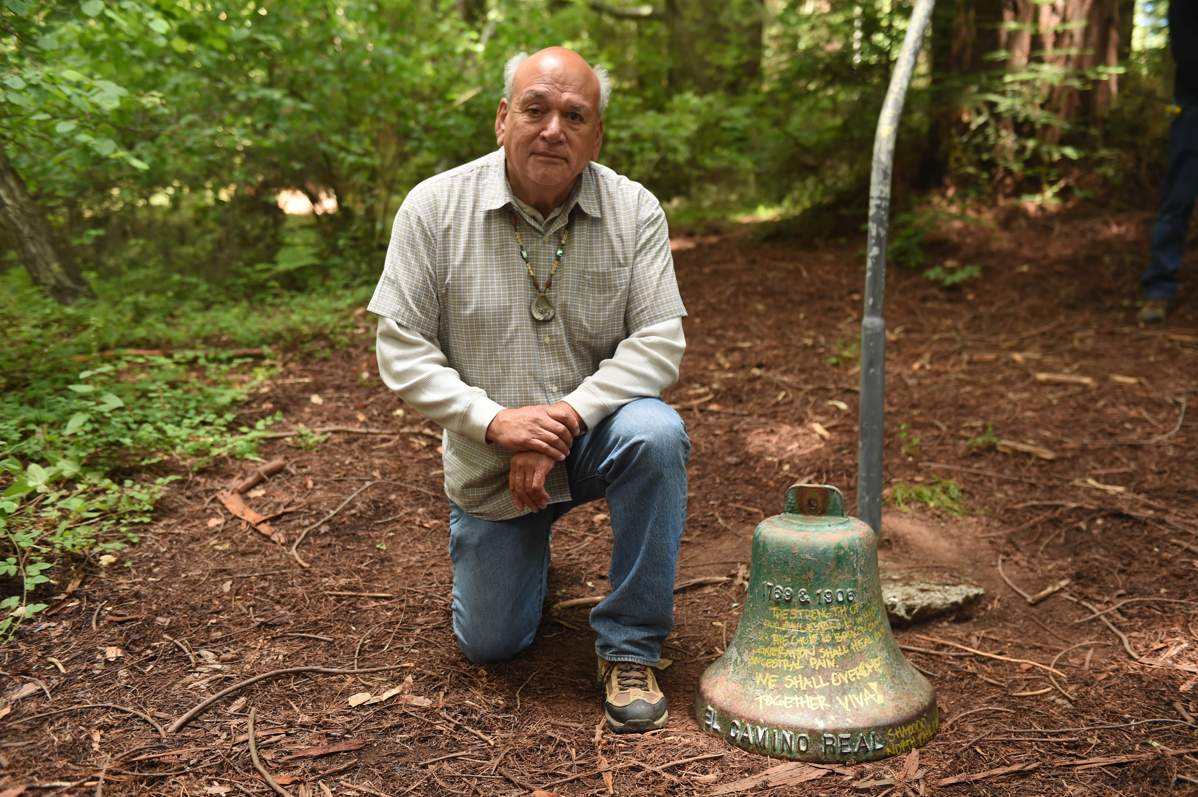 Chairman Val Lopez kneeling by a bell