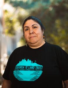 Corrina Gould in black t-shirt with Sogorea Te Land Trust logo
