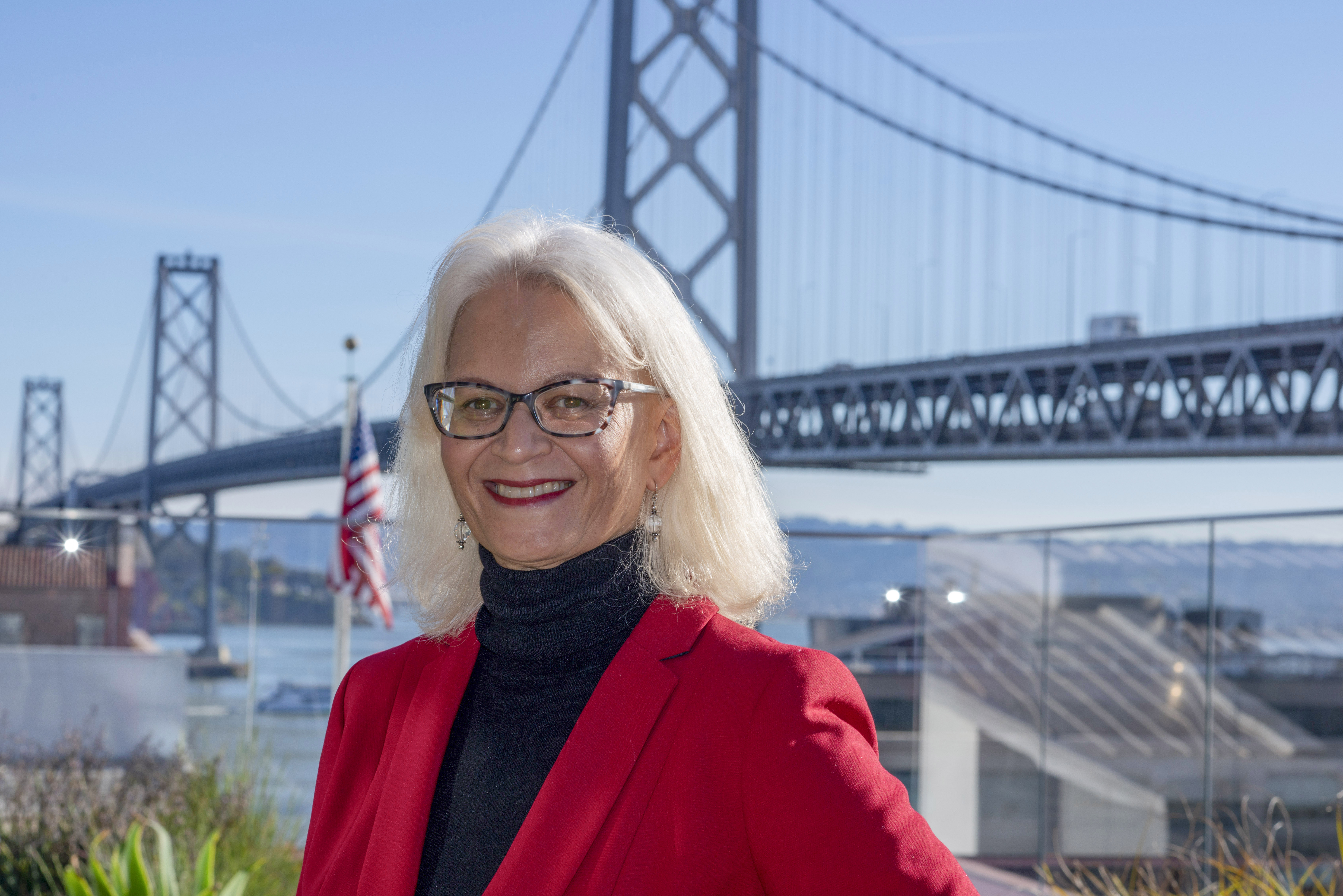 Therese McMillan wearing red blazer in front of Bay Bridge